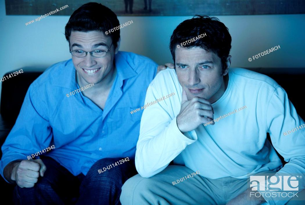 Stock Photo: Two men watching a game on television.