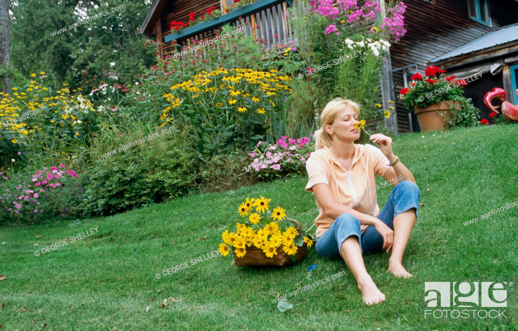 Stock Photo: woman smelling a flower.