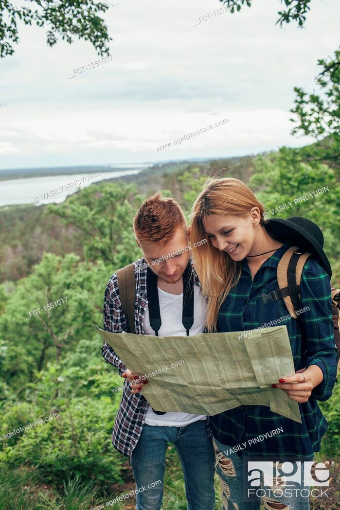 Stock Photo: Smiling couple reading map while hiking in forest.