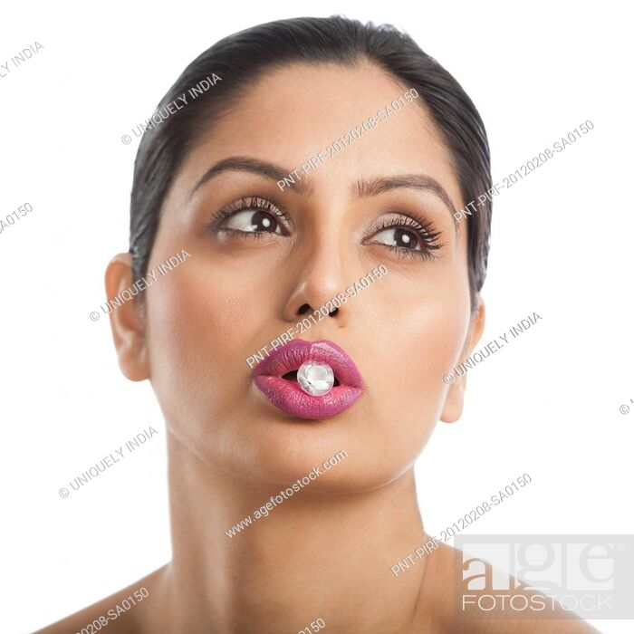 Stock Photo: Woman holding diamond between her lips.