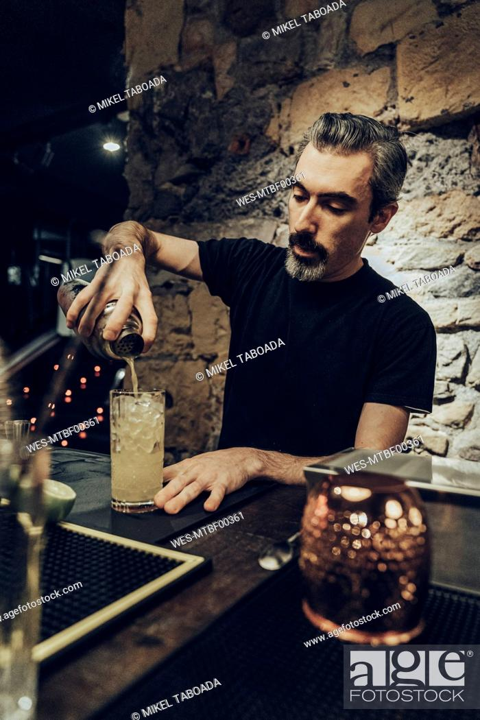 Stock Photo: Bartender pouring cocktail in a glass.