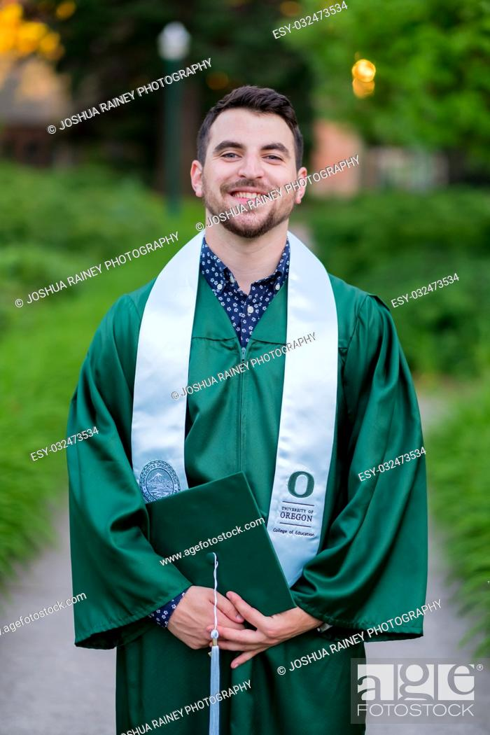 Stock Photo: EUGENE, OR - MAY 23, 2017: Male college student with cap and gown poses for a graduation photo on campus at the University of Oregon in Eugene.