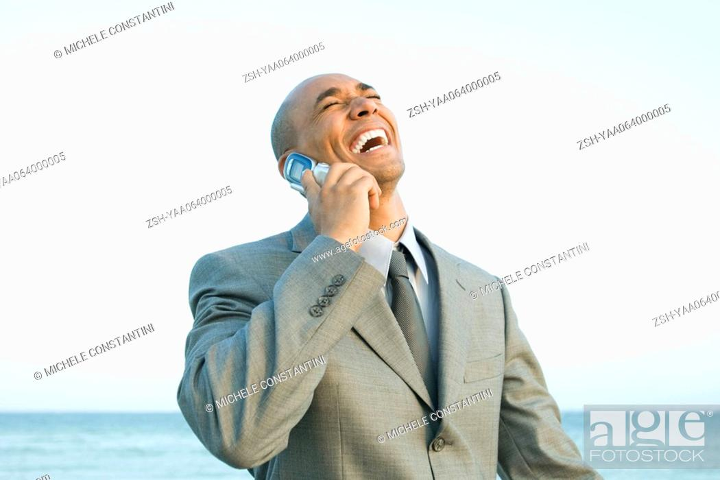 Stock Photo: Businessman at the beach using cell phone, laughing, eyes closed.
