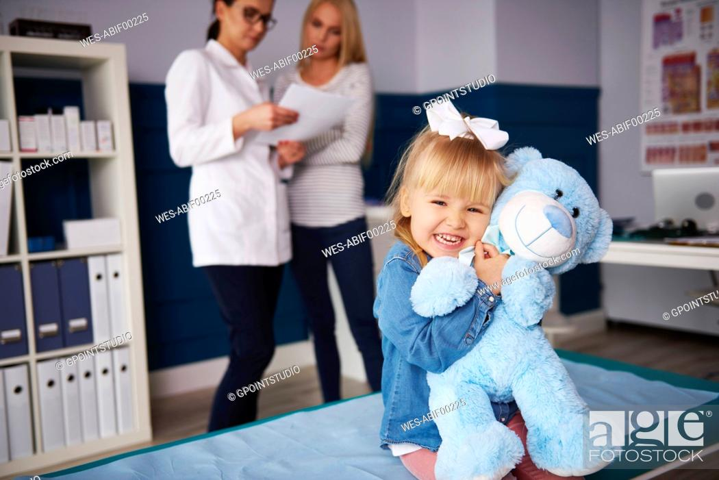 Stock Photo: Girl hugging teddy in medical practice with doctor and mother in background.