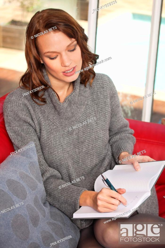 Stock Photo: Young woman writing in notebook.