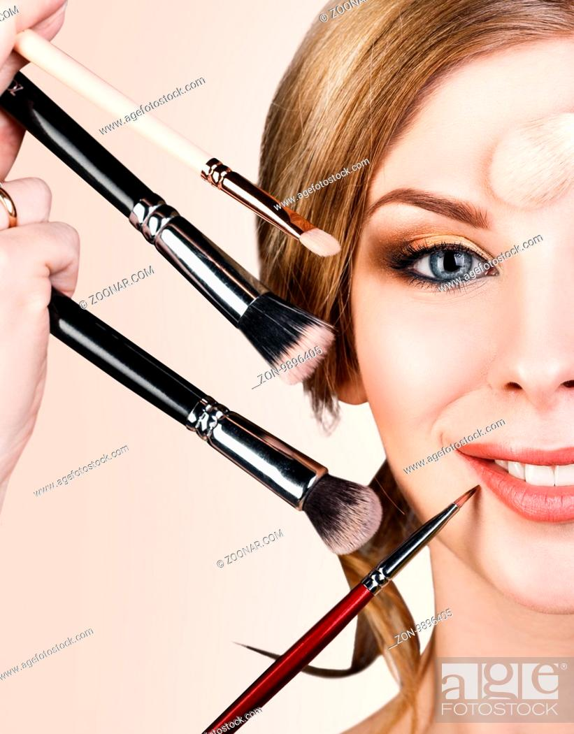 Photo de stock: Many hands with cosmetics brushes applying make-up to glamour woman, over beige background.