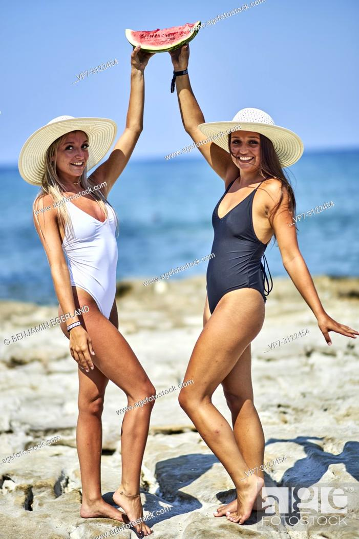 Stock Photo: Two young women with water melon and sunhats. Chersonissos, Crete, Greece.