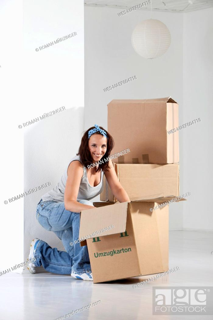 Stock Photo: Young woman packing cardboard box, smiling, portrait.