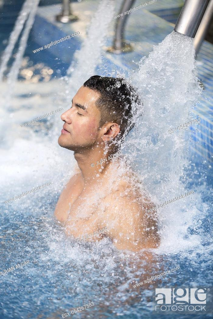 Stock Photo: Vertical indoors shot of man with eyes closed refreshing under shower in pool.