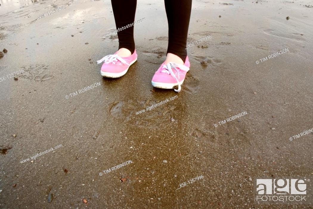 Stock Photo: Feet and legs of 7 year girl wearing pink plimsolls on beach.