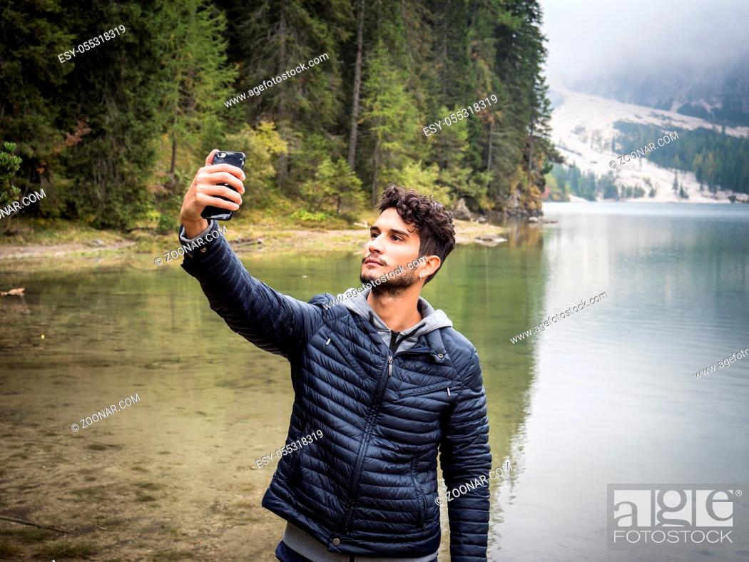 Photo de stock: Young handsome man taking selfie with smartphone at lake in forest.