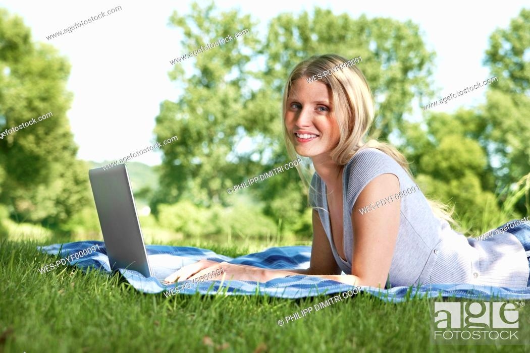 Stock Photo: Germany, Cologne, Young woman using laptop in meadow, smiling, portrait.