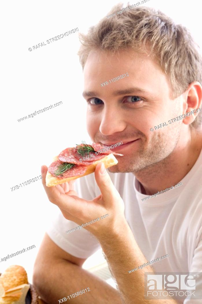 Stock Photo: man eating sandwich with salami.