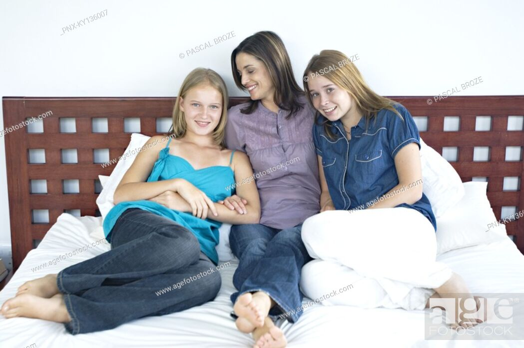 Stock Photo: Mother and two teenagers sitting on a bed, indoors.