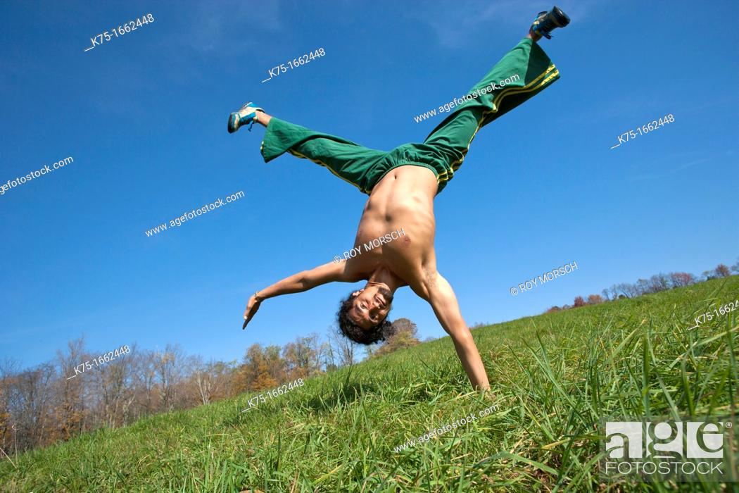 Stock Photo: One arm handstand in field.
