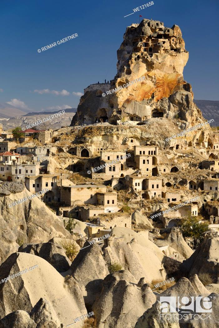 Stock Photo: Fairy Chimneys Houses and Ortasihar Castle rock being repaired as a museum Cappadocia Turkey.
