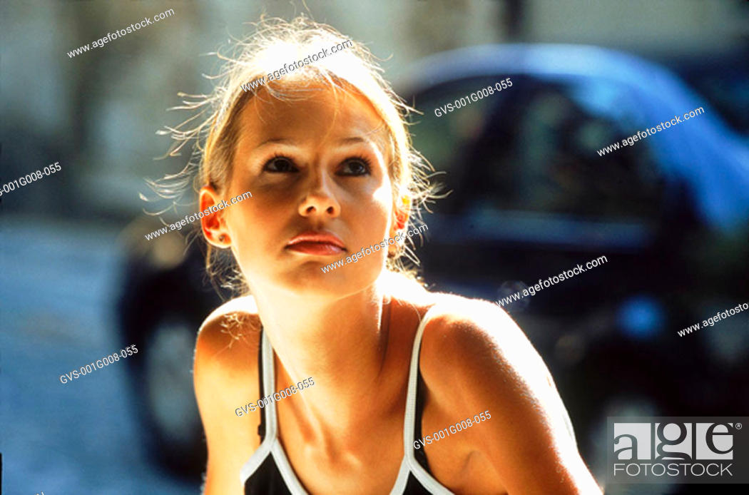 Stock Photo: Young woman sitting and looking up.