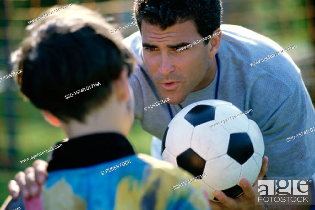 Stock Photo: Soccer coach standing with his hand on a boy's shoulder.