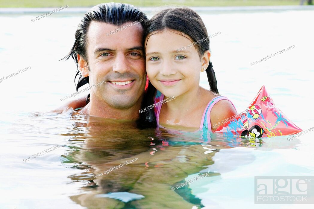 Stock Photo: Portrait of a man and his daughter smiling in a swimming pool.