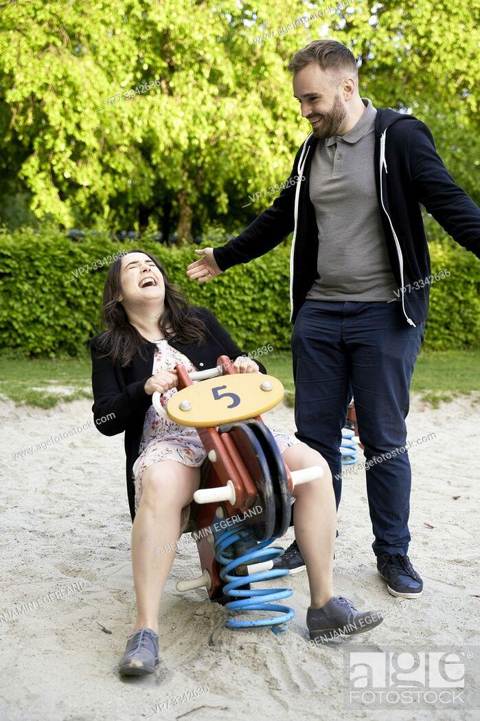 Stock Photo: playful adult couple enjoying free time on playground, carefree, playground rocker.