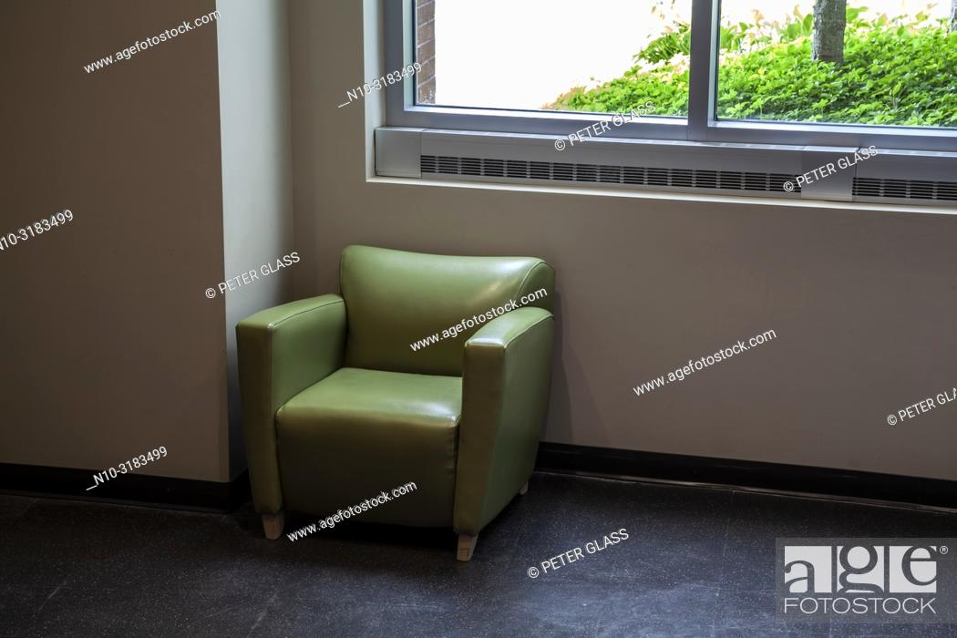 Photo de stock: Soft chair by a window in an office building lobby.