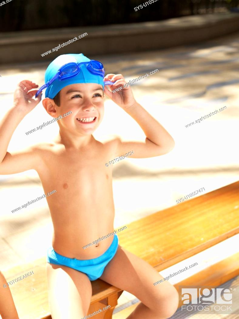 Stock Photo: Boy in swimming trunks adjusting goggles.