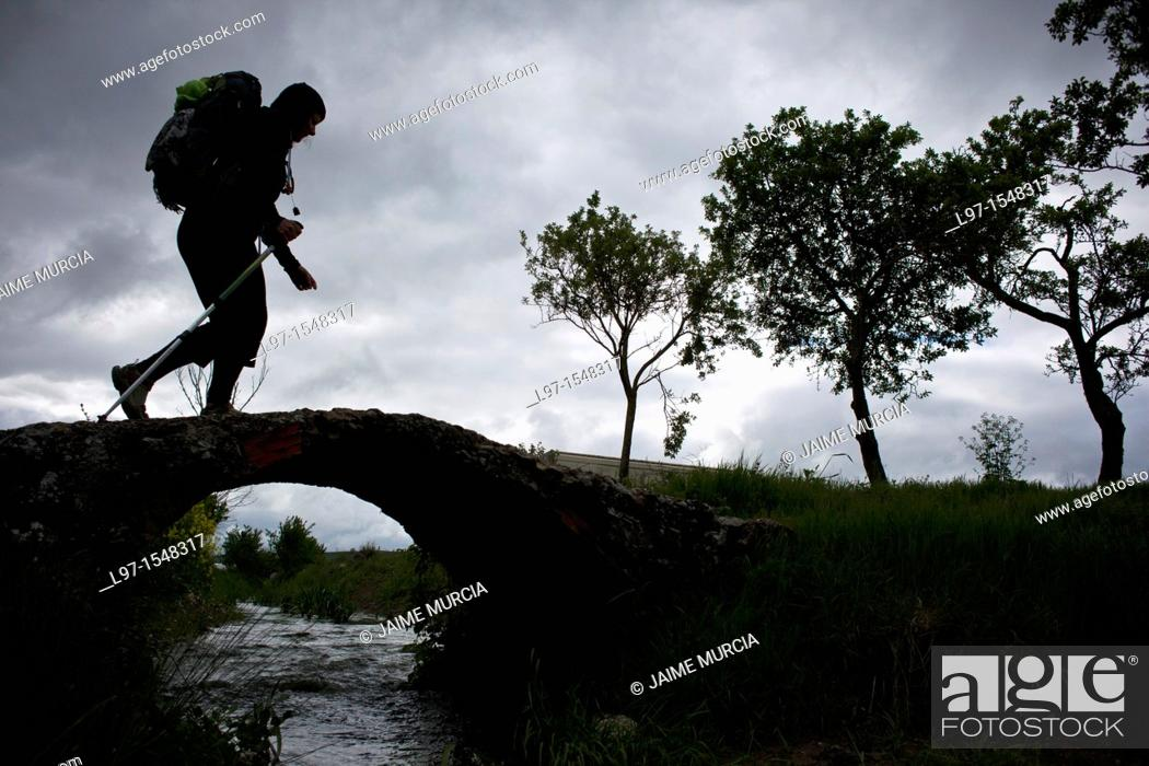 Stock Photo: Silhouette of hiker crossing bridge along the Camino de Santiago, route Frances.