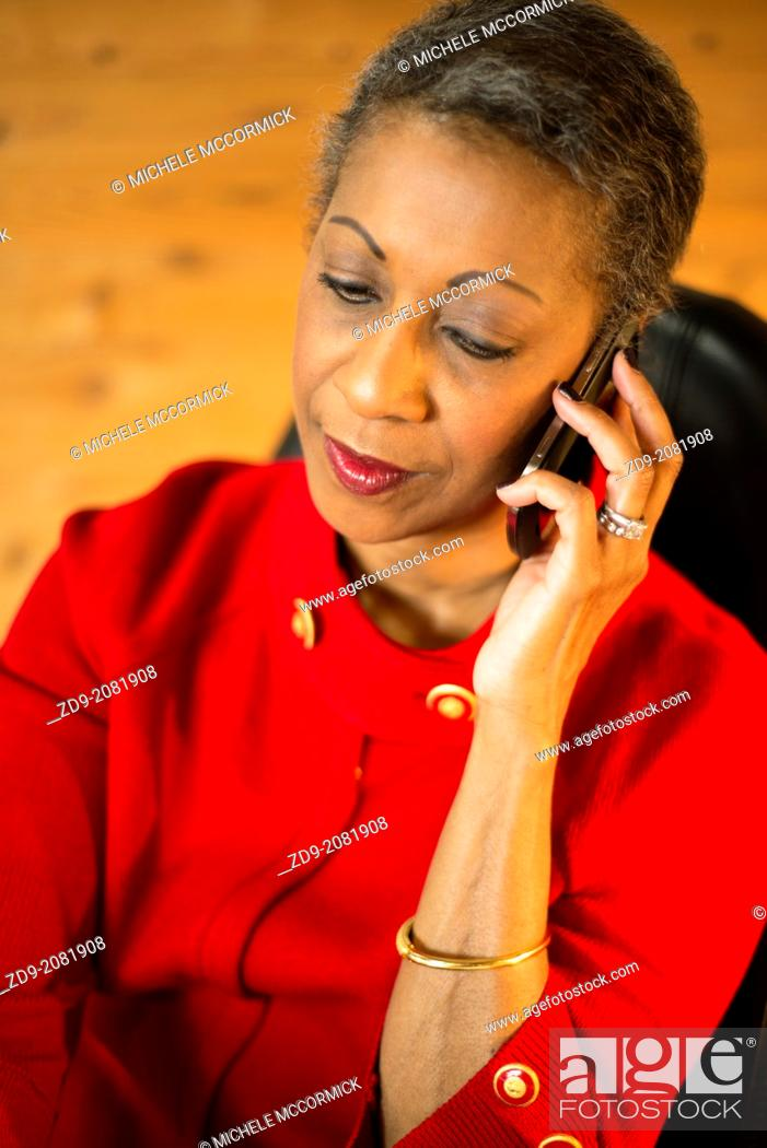 Stock Photo: An attractive middle-aged professional black woman talks on her cell phone.