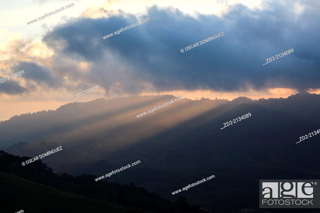Stock Photo: Sunrise and light beams over forested hillsides. Doi Pha Hom Pok National Park. Thailand.