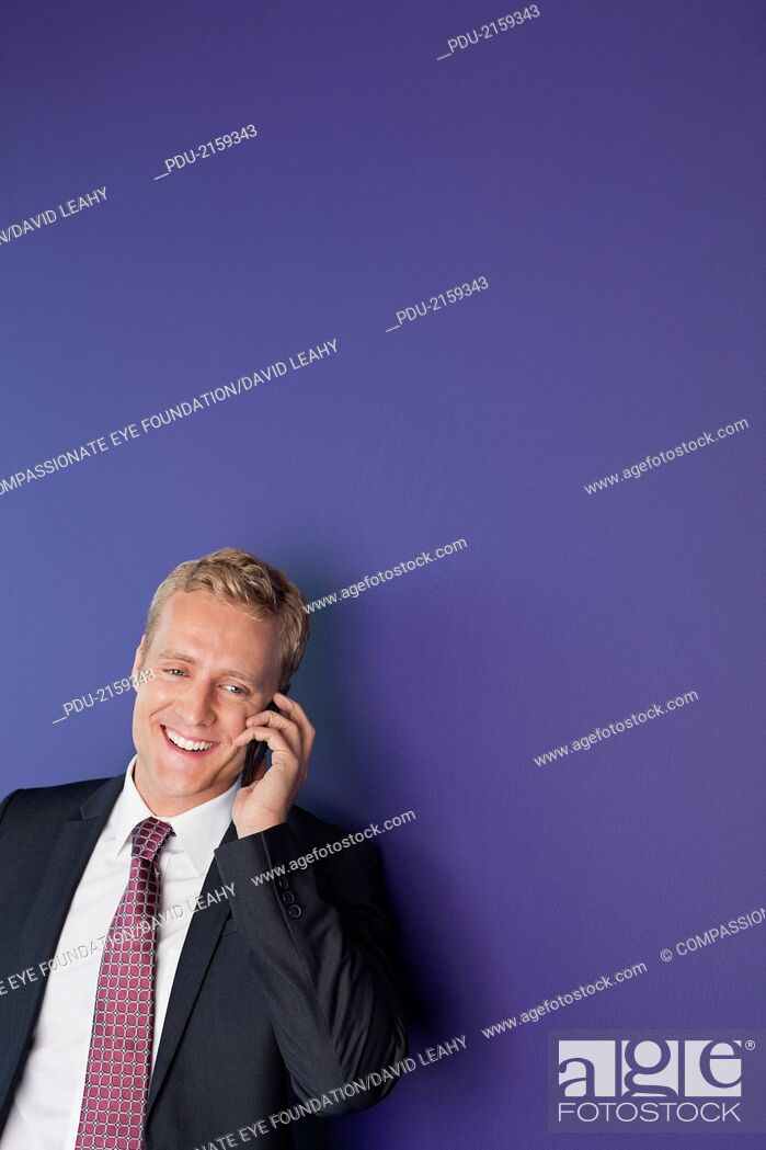 Stock Photo: Smiling businessman using cell phone.