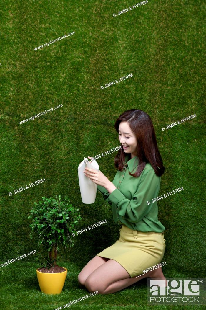 Stock Photo: A woman watering the tree.
