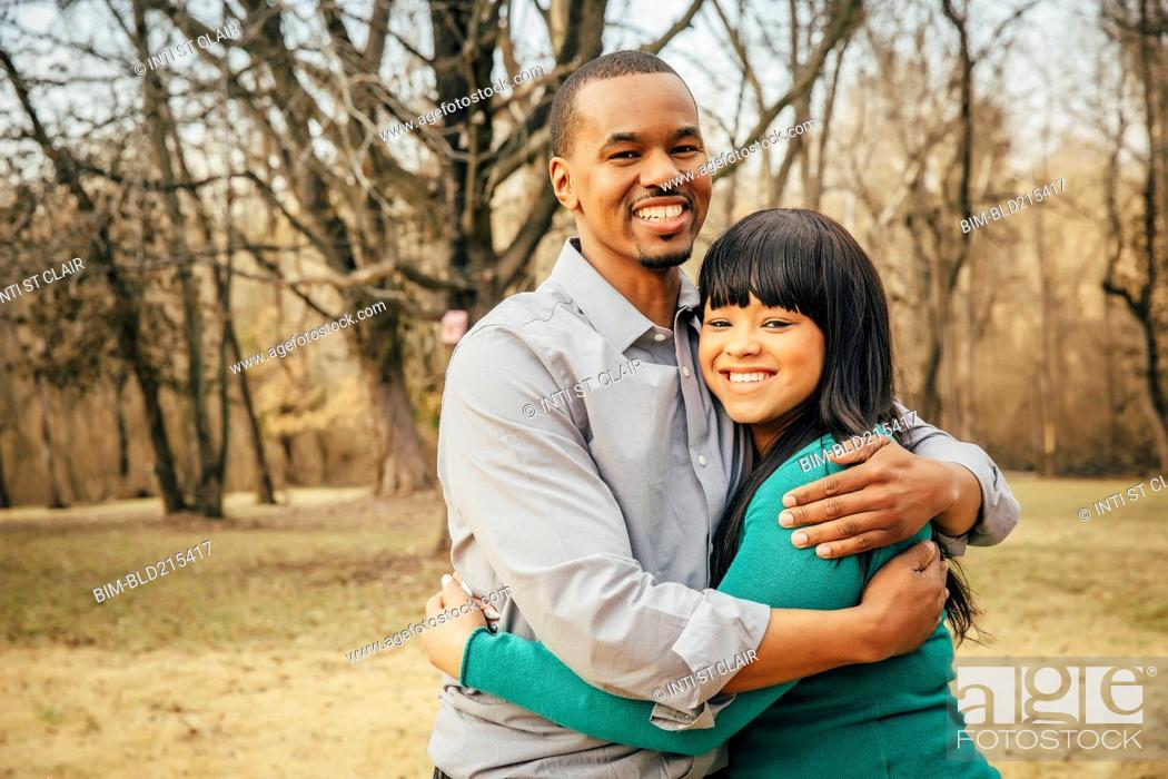 Stock Photo: Black father and daughter hugging outdoors.