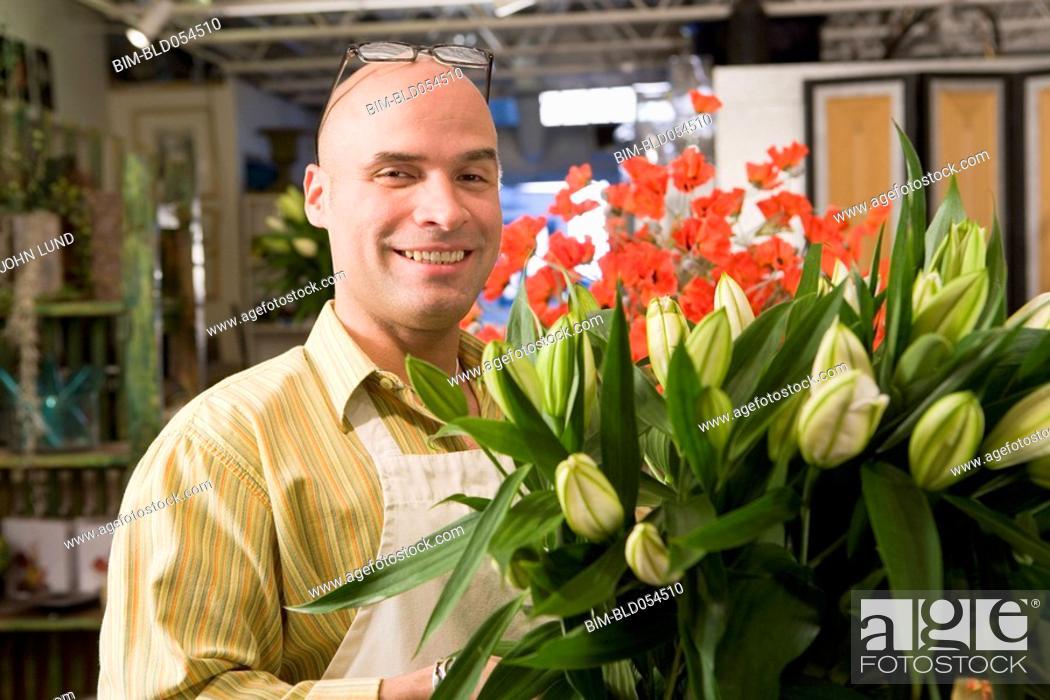Stock Photo: Hispanic male florist arranging flowers.
