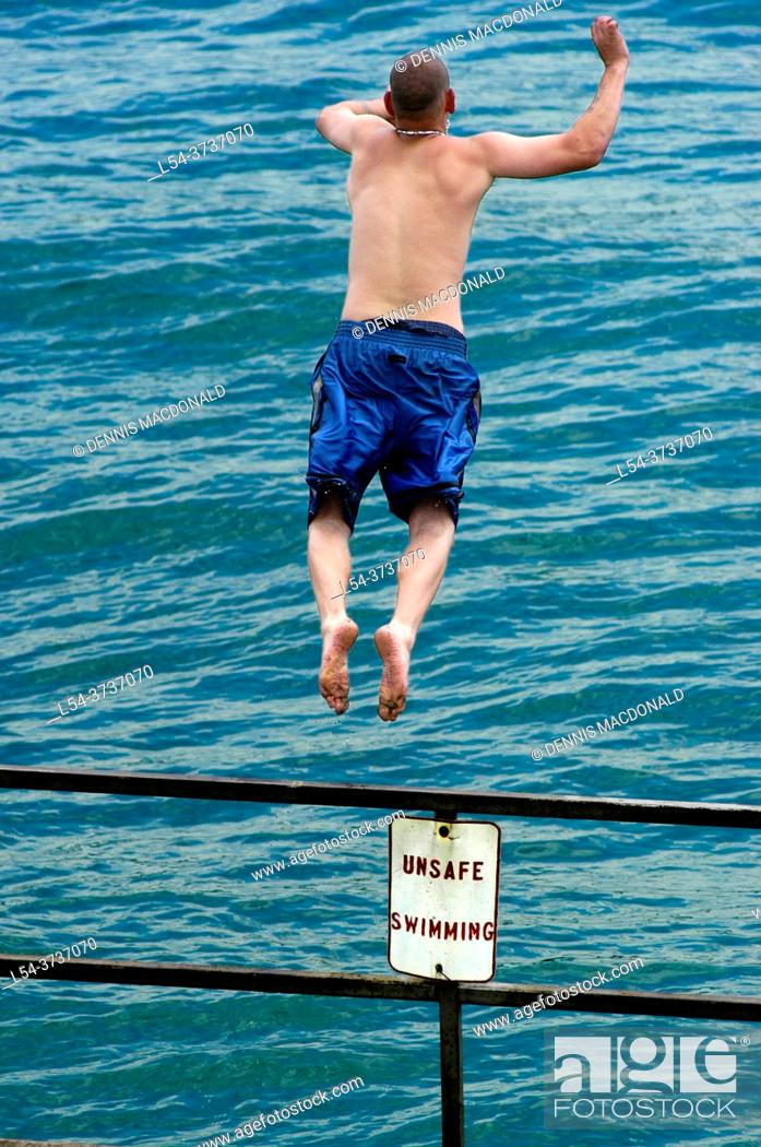 Stock Photo: Male jumping off of a railing into water with sign saying Unsafe for swimming.
