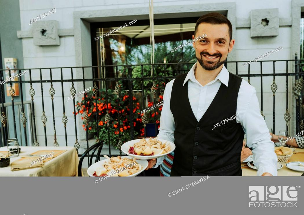 Stock Photo: Uniformed waiter serving plates of food and smiling for the camera; Italy.