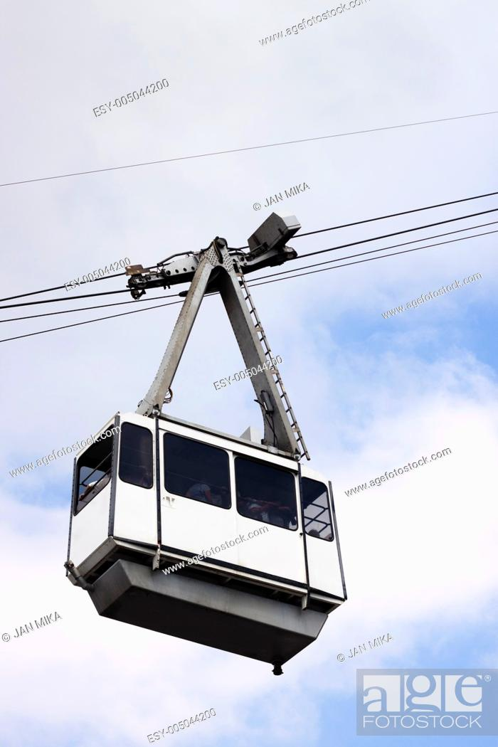 Stock Photo: Cable Car on wires over cloudy sky with non-recognisable silhouettes of people inside  Cable Car in Gibraltar.