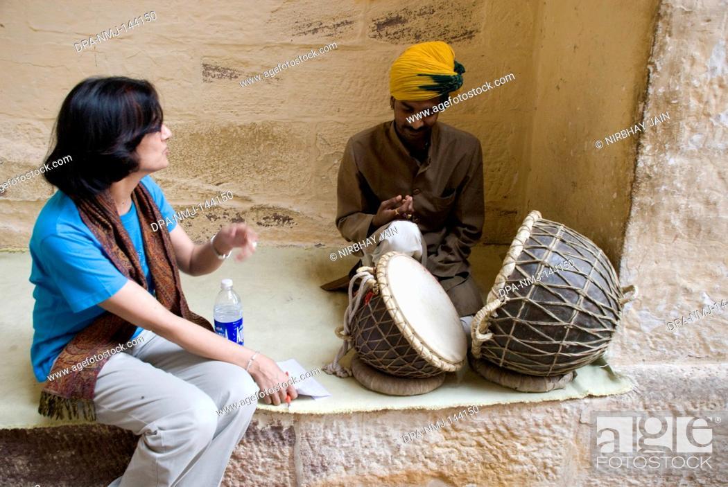 Stock Photo: A Young lady watching musician who playing drums at Mehrang Garh fort at Jodhpur ; Rajasthan ; India NO MR.