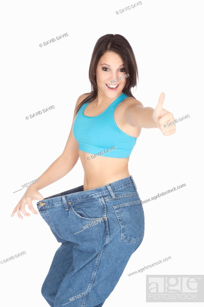 Stock Photo: Woman showing weight loss by wearing an old pair of jeans.