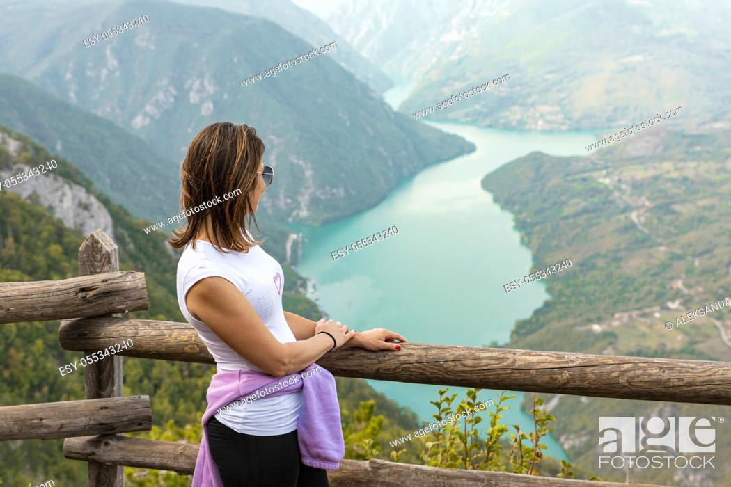 Stock Photo: Woman hiker at mountain viewpoint enjoying the view of a lake and canyon.
