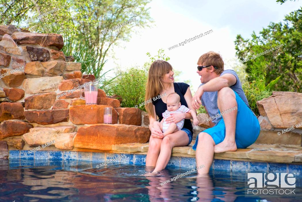 Stock Photo: Parents with baby boy sitting at swimming pool, smiling.