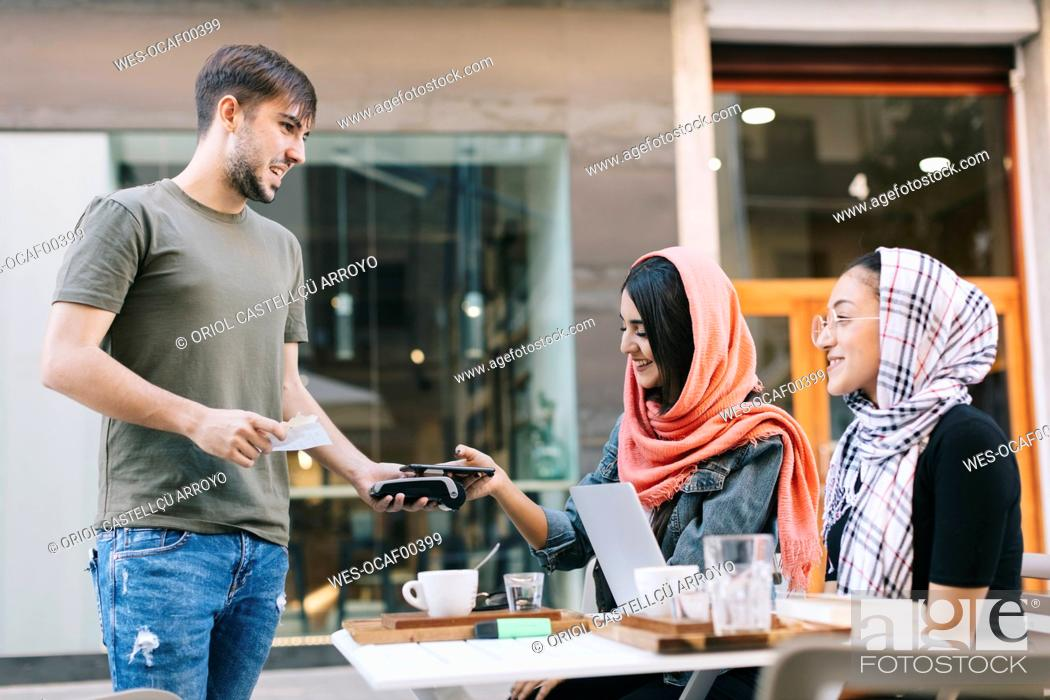 Stock Photo: Young woman paying cashless with smartphone in a cafe.