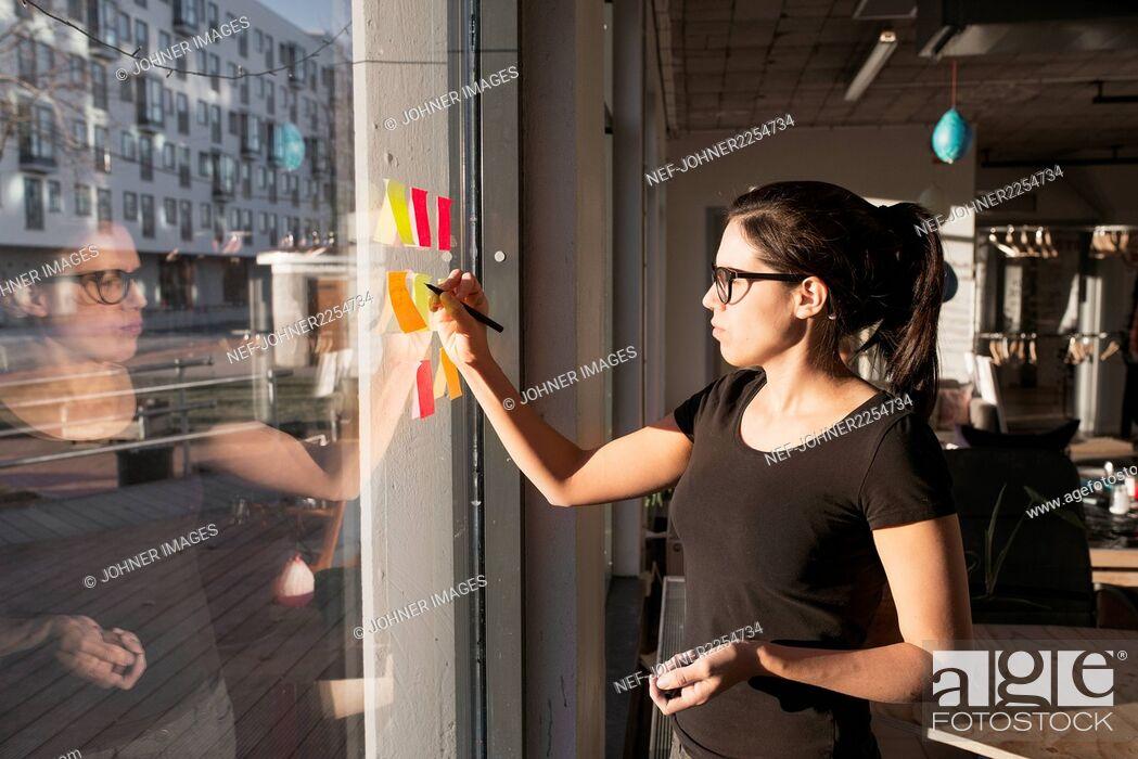Stock Photo: Woman sticking notes on window.