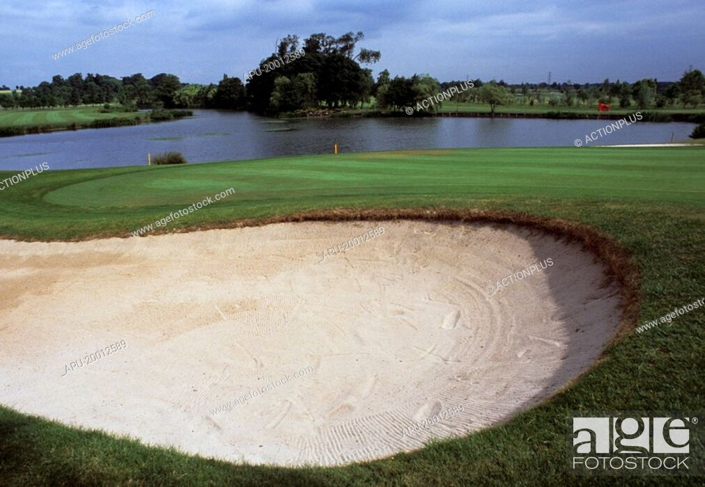 Stock Photo: Golf course green seen across a large bunker with lake in background.