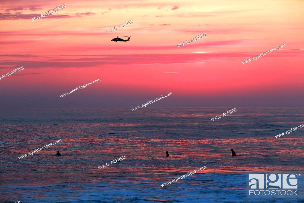 Stock Photo: Silhouette of helicopter flying above men swimming in sea at sunset, Windansea Beach, La Jolla, San Diego, California, USA.