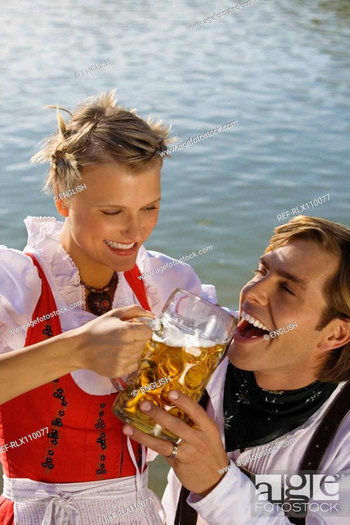 Stock Photo: Young couple in traditional Bavarian outfit, woman giving man drink of beer.