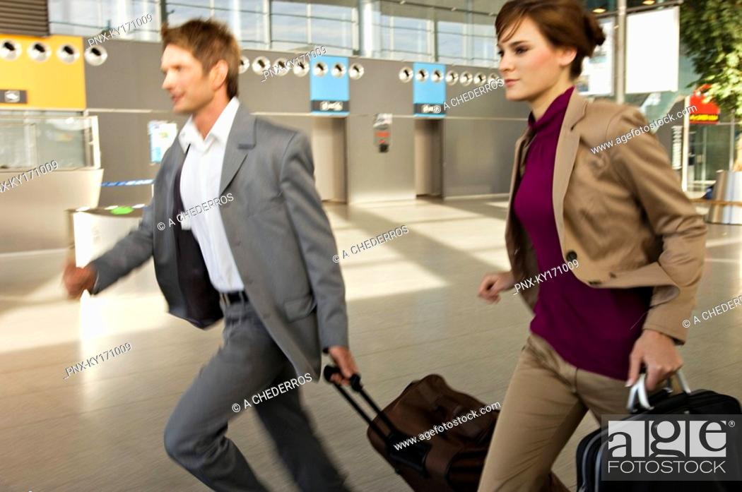 Stock Photo: Businessman and a businesswoman rushing with their luggage at an airport.