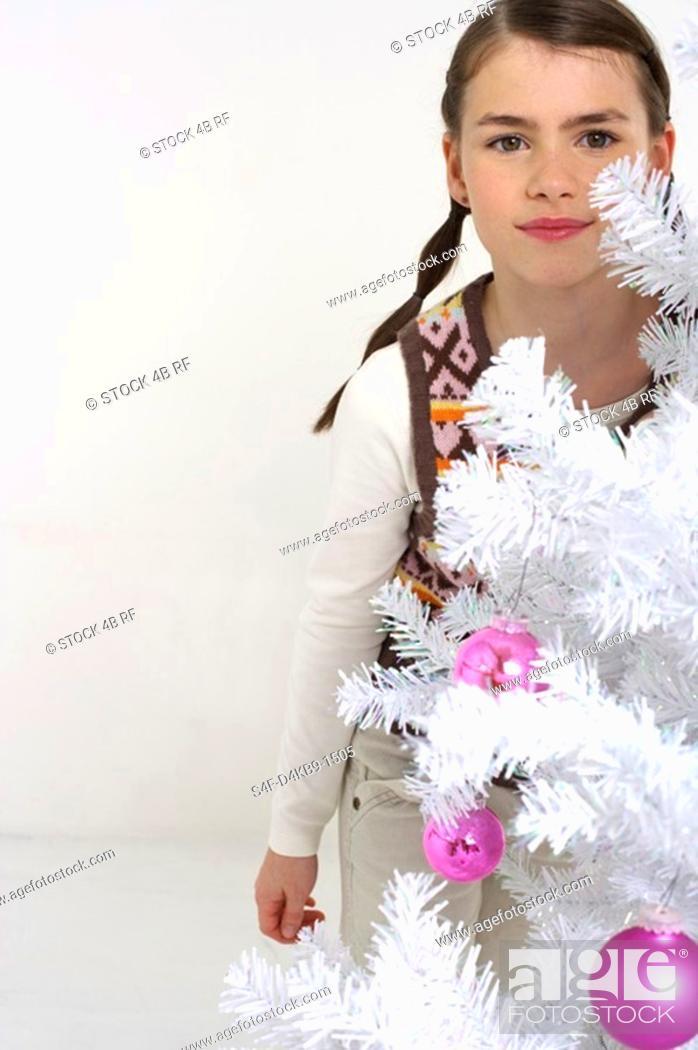 Stock Photo: Girl next to a white Christmas tree.