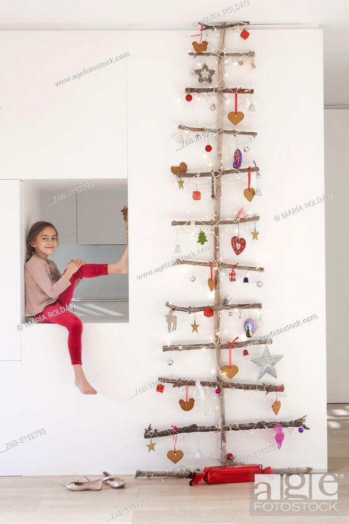 Stock Photo: Little girl seated by a Christmas tree.