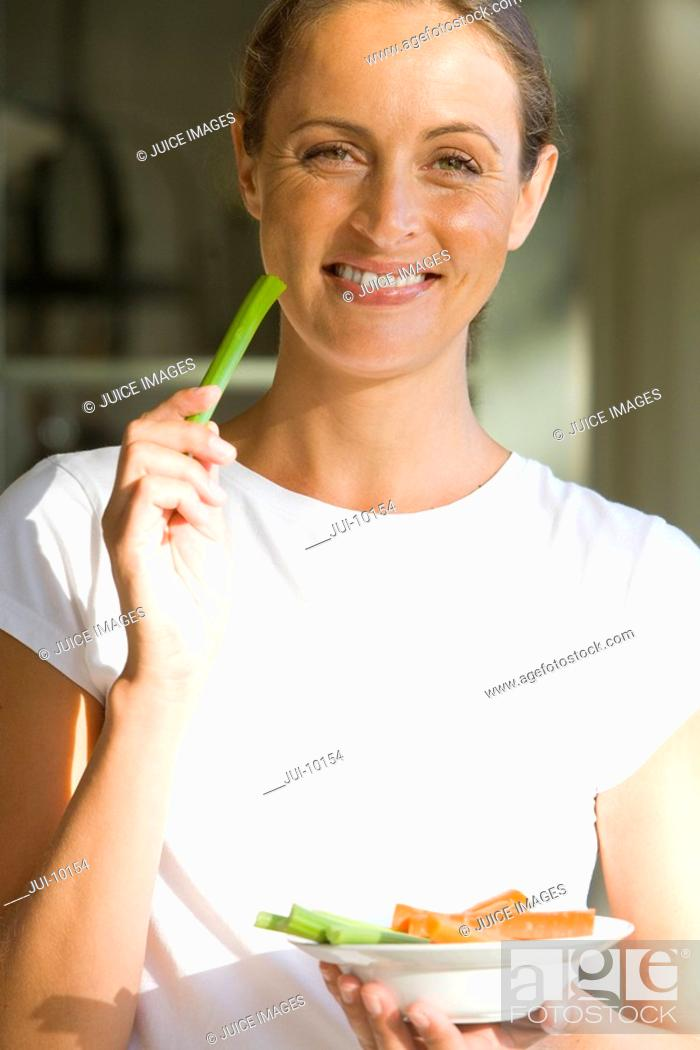 Stock Photo: Woman with bowl of vegetable sticks, smiling, portrait.