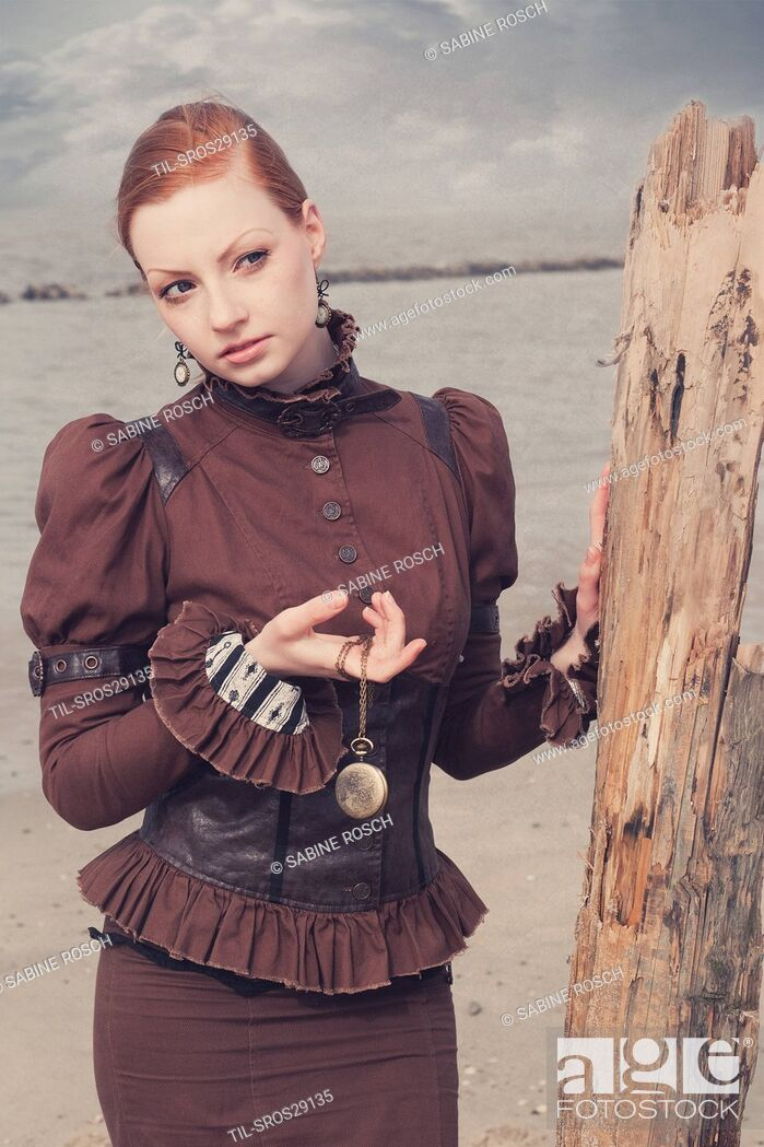 Stock Photo: Young woman in a victorian dress standing alone outdoors beside the sea and holding a pocket watch in her hand.